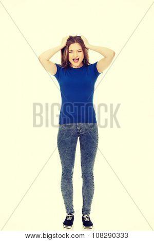 Angry teenage woman holding her head.