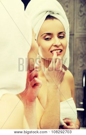 Beautiful woman takes off the dirt from her teeth.