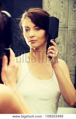 Brunette woman brushing hair in front of bathroom mirror.