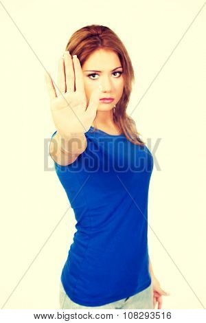 Young woman making stop sign with her hand.