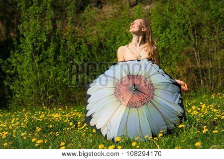 Undressed woman is covered with umbrella in a flowery meadow