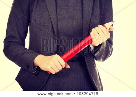 Business woman holding oversized pencil.