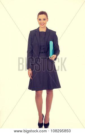 Happy businesswoman holding a binder.
