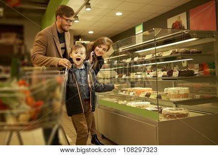 Family near display with cakes in a grocery store