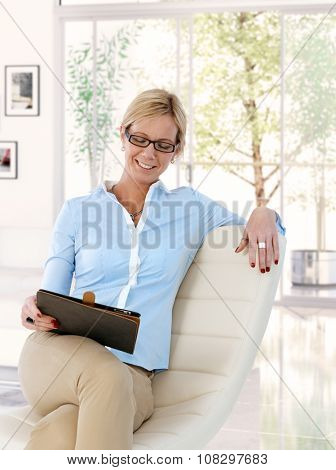 Happy mid adult caucasian blonde casual businesswoman at home with tablet computer. Sitting in chair, looking at screen, wearing glasses, smiling, checking business.  .