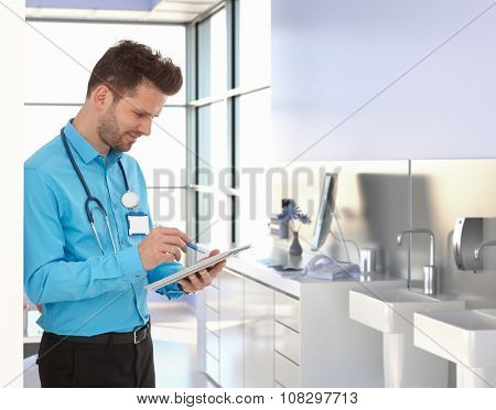 Busy male physician working with tablet in doctors office.