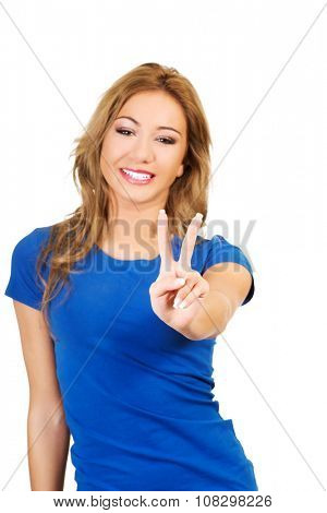 Young happy woman showing victory sign.
