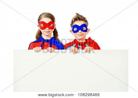 Boy and girl teenagers in a costume of superheroes holding white board. Isolated over white background.