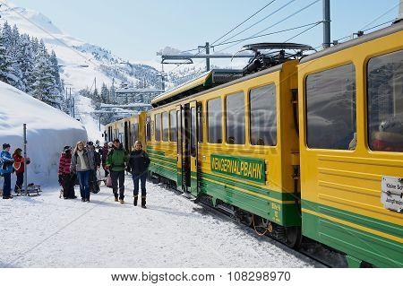 People walk by the Wengernalpbahn railway platform in Grindelwald, Switzerland.