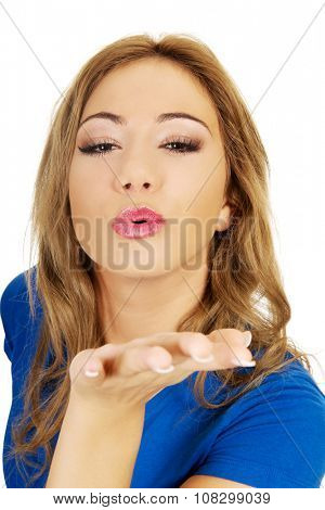 Young beautiful woman blowing a kiss.