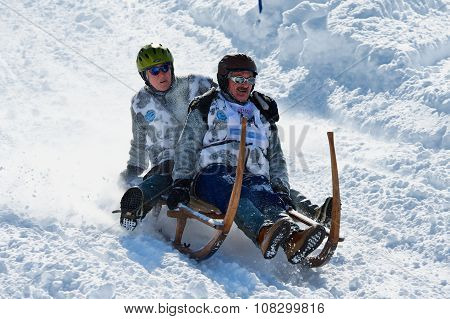 People ride traditional horn-sledge at 12-th annual Horn-Sledge Race in Grindelwald.