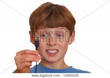 Irritated Boy Looks At A Usb Jack