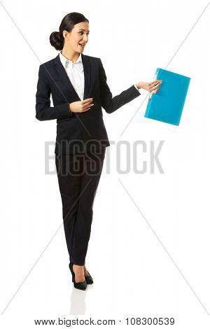 Full length businesswoman holding a binder.