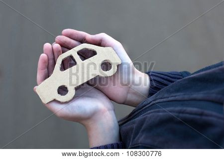 Young Homeless Boy Holds A Cardboard Car
