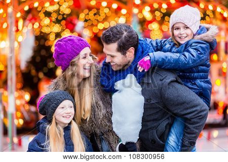 Family eating cotton candy on Christmas market