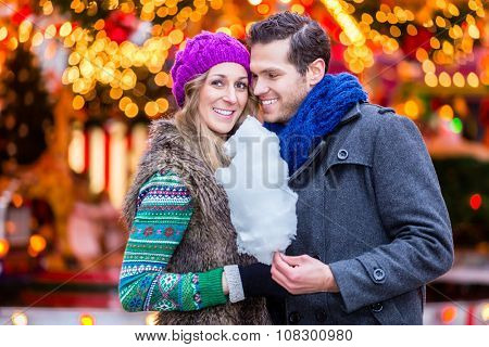 Couple on Christmas market eating cotton candy