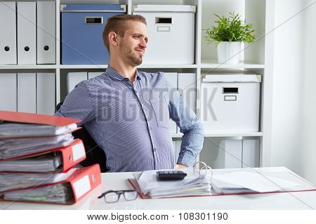 Young Businessman Has Backache At Work In Office