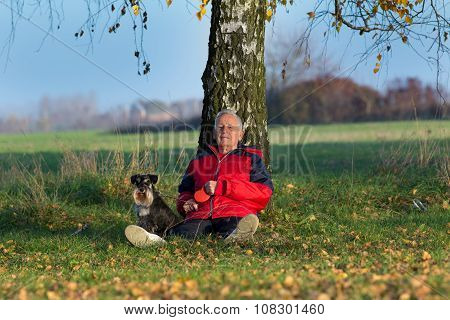 Senior Man With Dog Sitting On Grass Leaning On Tree