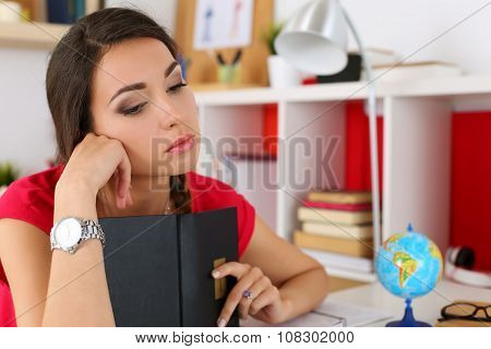 Sad Young Female Student In Red Dress Covering Head With Book And Looking Down. Tired Woman In Despa