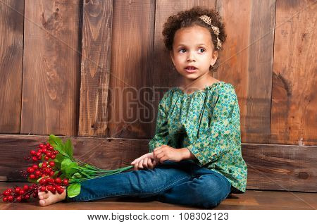 Little African  Girl In Rural Shirt With Bunch Of Berries. Background Of Brown Wooden Wall