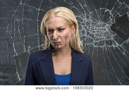 Sad woman stands against broken glass