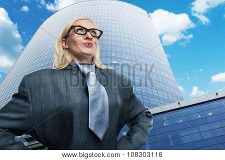 Surprised geek businesswoman near the skyscraper