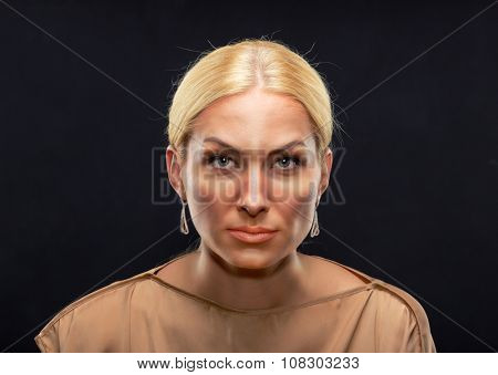 Blond serious adult woman looking at you over black