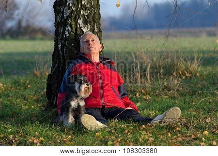 Senior Man With Dog Sitting In Forest