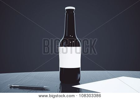 Black Beer Bottle On Black Table With Paper And Pen At Black Background, Mock Up