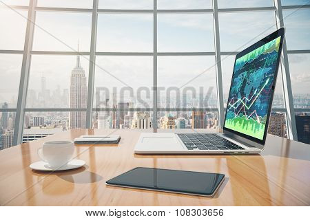 Sunny Office With Megapolis City View, Digital Tablet And Laptop Screen With Business Chart On The W