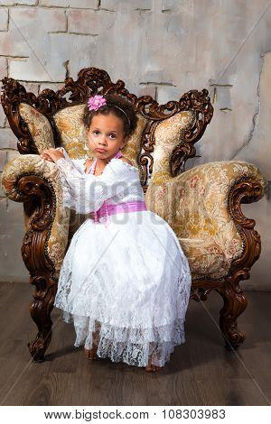 Cute African  Girl With Curly Hair In A White Lace Dress On Vintage Chair