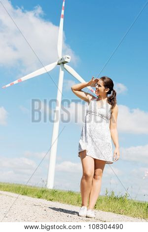Happy teen girl next to wind turbine.Eco energy concept.