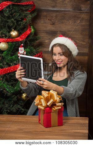 Beautiful girl making selfies on tablet PC near New Year tree