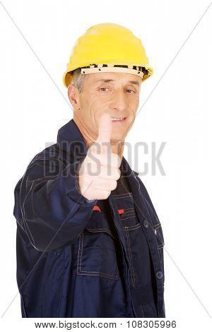 Mature repairman gesturing ok sign.