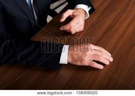 Mature businessman's hands put on the desk.