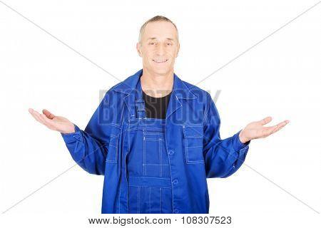 Mature repairman holding copyspace in both hands.