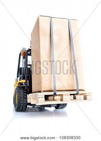 Forklift truck carrying goods packed in cardborad box placed on wooden pallet shot on white background
