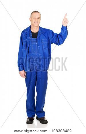 Smiling mature repairman pointing up.