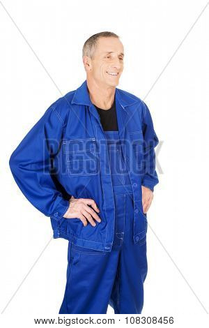 Happy mature repairman with hands on hips.