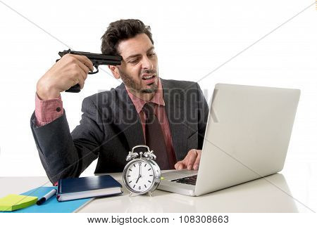 Businessman At Office Desk Working On Computer Laptop Pointing Gun On His Tempo In Suicide Gesture