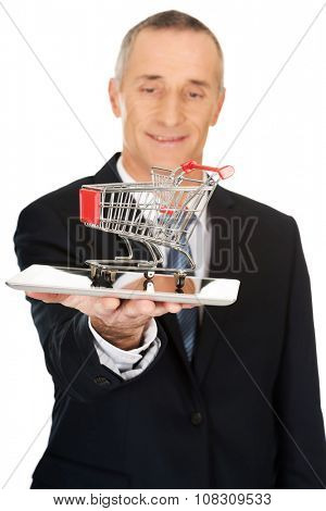 Mature businessman holding shopping cart on tablet.