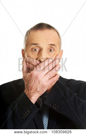 Portrait of businessman covering mouth.
