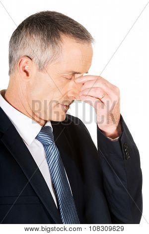 Mature businessman suffering from sinus pain.