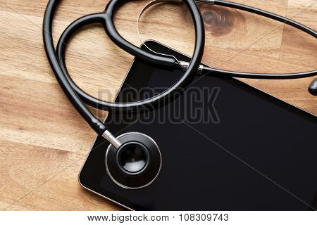 stethoscope and computer tablet on wooden table