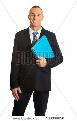 Smiling mature businessman holding a binder.
