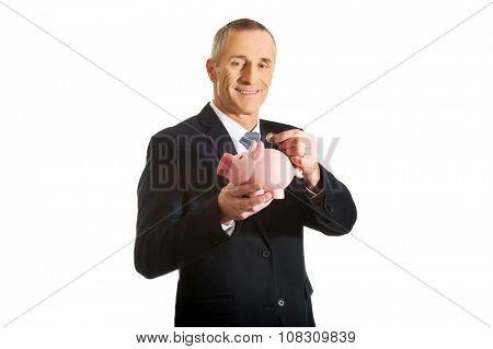 Mature businessman putting a coin to piggybank.