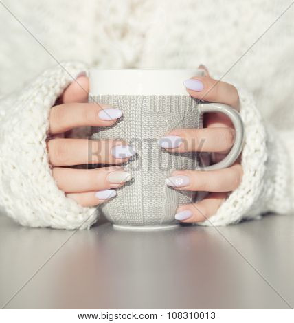 Close up of woman's hands holding cup of hot coffee drink. She is wearing warm cardigan. Winter chill out and lifestyle concept.