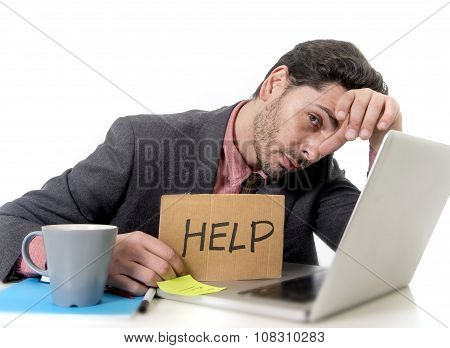 Businessman In Suit And Tie Sitting At Office Desk Working On Computer Laptop Asking For Help Holdin