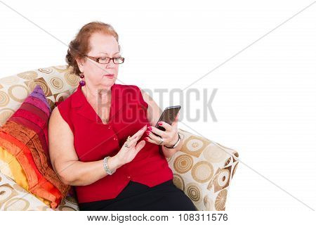 Senior Woman Sitting On Couch Using Her Phone