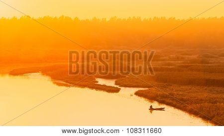 River and rowing fishing boat at beautiful sunrise in autumn morning. Fisherman is in the boat